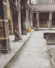 A Monk awaits prayer in Angkor Wat, Siem Reap, Cambodia
